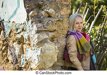 Young fashion woman near old stone walls in the Park.