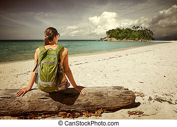 Young woman with backpack relaxing on coast and looking to a...