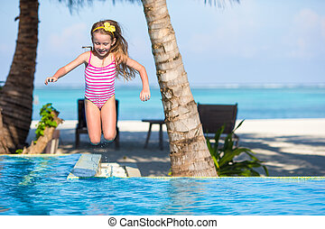 Smiling adorable girl having fun in outdoor swimming pool -...