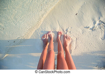 Closeup mother and kid feet on white sand beach - Closeup...