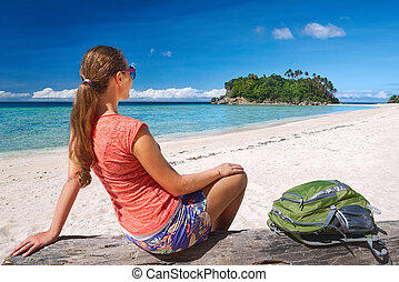 Happy young woman with backpack relaxing on coast and...