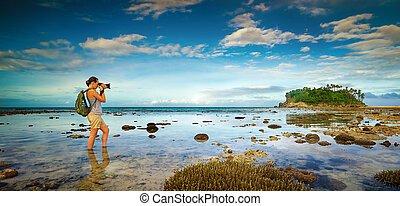 standing in the water traveler woman with backpack taking a...