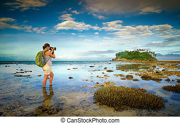 standing in the sea water traveler woman with backpack...
