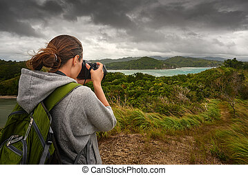 Travelling woman photographer with backpack making an...