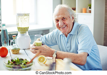 Senior man in the kitchen - Senior man with glass of fruit...