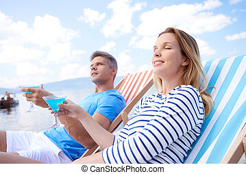 Happy summer - Young man and woman with martini relaxing at...