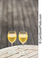 Two glasses of tasty white wine at sunset on wooden table -...