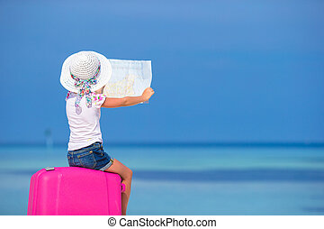 Little adorable girl with big luggage and map of island on...