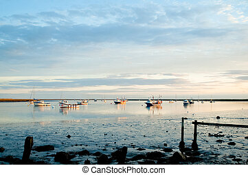 estuary sunset - fishing boats moored in a tidal estuary at...