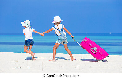 Little adorable girls with big suitcase on tropical white...