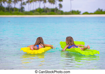 Adorable little girls on inflatable mattress in the sea...