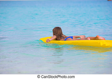 Adorable little girl on air inflatable mattress in the sea -...