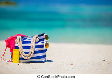 Blue bag, swimsuit, sunglasses and suncream on white beach -...