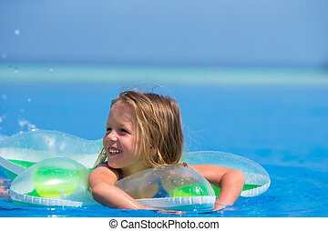 Little happy cute girl in outdoor swimming pool - little...