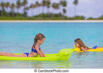 Adorable little girls on air inflatable mattress in the sea...