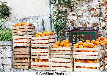 oranges in wooden boxes on street market