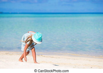 Adorable happy smiling little girl in hat on beach vacation...