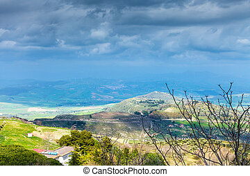 rainy clouds over green sicilian hills in spring - dark blue...