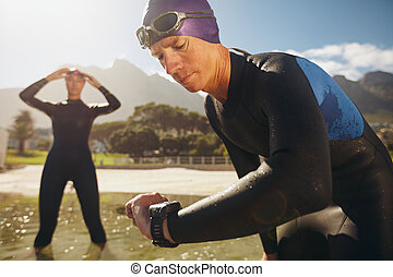 Triathletes practicing for race - Focused young man checking...