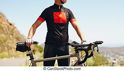 Cyclist standing with his bike - Outdoors - Mid section...