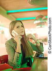 Young woman talking on a cell phone in cafe