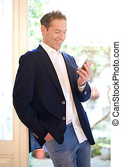 Happy businessman looking at mobile phone