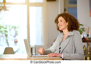 Happy middle aged woman using laptop at home