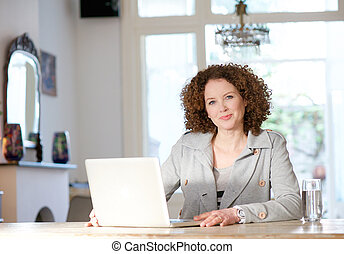 Mid adult woman using computer at home - Portrait of a mid...