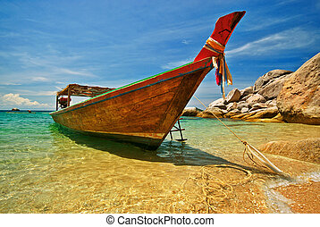 Longtail Boat - Longtail boat anchored at a beach