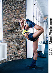 Sporty woman stretching at gym - Full length portrait of a...