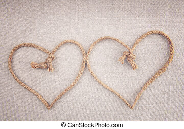 Two love hearts made of string crossed together on fabric...