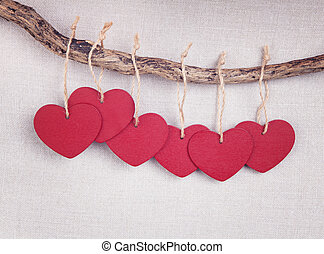 Red wooden heart hanging on the branch
