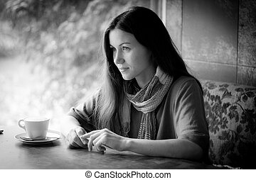 Beautiful young woman with a cup of tea at a cafe