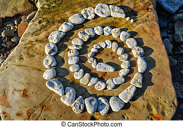 Wind-down - Spiral of pebbles on the sea boulder