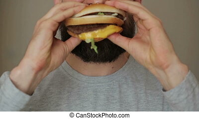 Man eats a hamburger - time lapse - Beared man eats a...