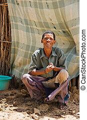 basarwa man - One of the few remaining bushman sitting down...