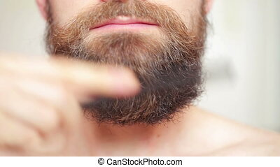 man combing his mustache and beard - %u0421are beard - man...