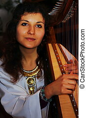 Young woman playing celtic harp in a historical costume -...