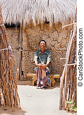 basarwa man - One of the few remaining bushman sitting down...