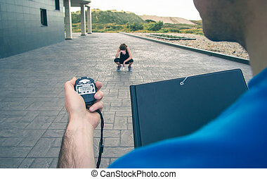 Trainer hand using chronometer to timing woman training -...