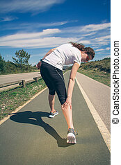 Athletic woman suffering pain in leg calf by cramp - Back...
