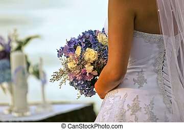 A rear view of a bride holding a bouquet