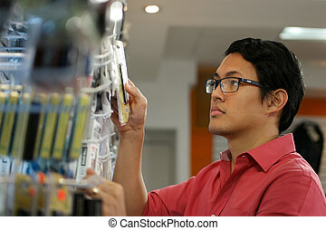Chinese Man Ordering Usb Drive On Shelf In Computer Shop -...