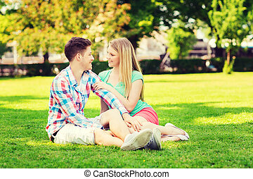 smiling couple sitting on grass in park - holidays,...