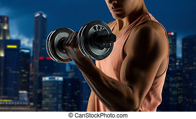 close up of young man with dumbbell flexing biceps - sport,...
