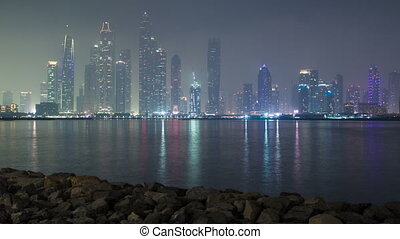 Dubai Marina skyline as seen from Palm Jumeirah, Dubai, UAE.  Timelapse