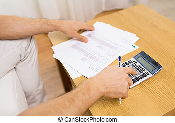 close up of man with papers and calculator at home -...