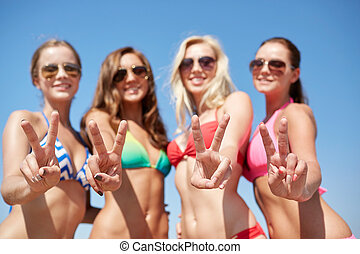 group of smiling young women on beach - summer vacation,...