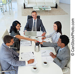 Businesswoman and businessman shaking hands in a meeting -...