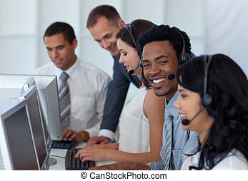 Manager talking to his business team in a call center -...